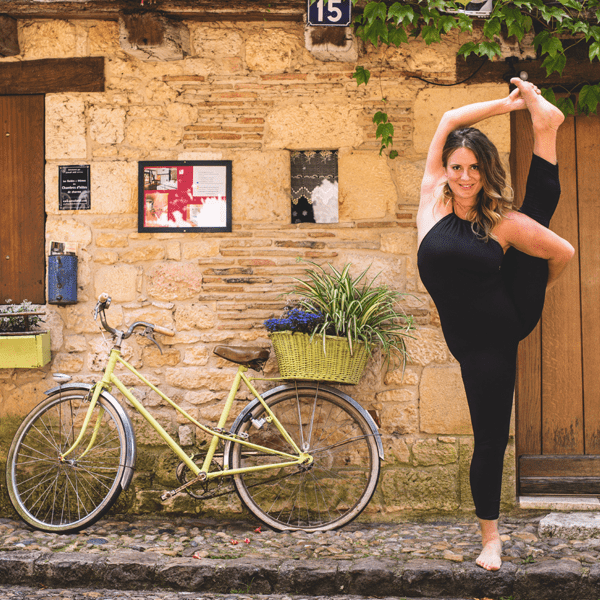 A woman poses in bird of paradise next to a bicycle on this yoga retreat in France with The Travel Yogi.
