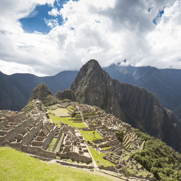 Machu Picchu bathed in sunlight with mountains in the background. Experience Machu Picchu on this Peru yoga retreat with The Travel Yogi.