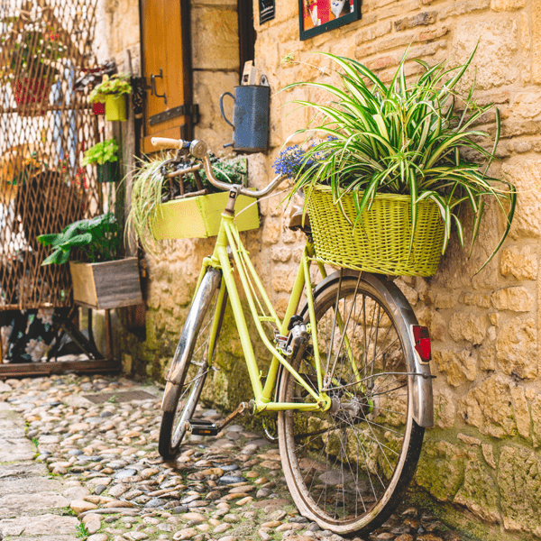A yellow bicycle with a basket lies against a building on this yoga retreat in France with The Travel Yogi.
