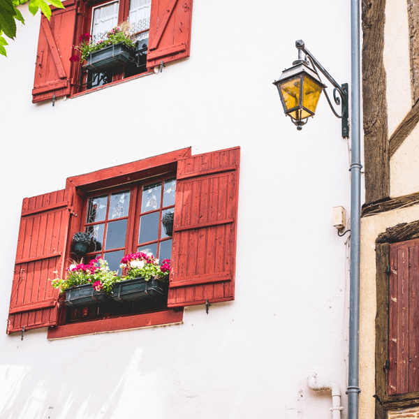 Red shutters on a white building on this yoga retreat in France with The Travel Yogi.