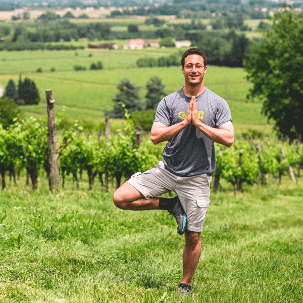 A man in tree pose in a field on this yoga retreat in France with The Travel Yogi.