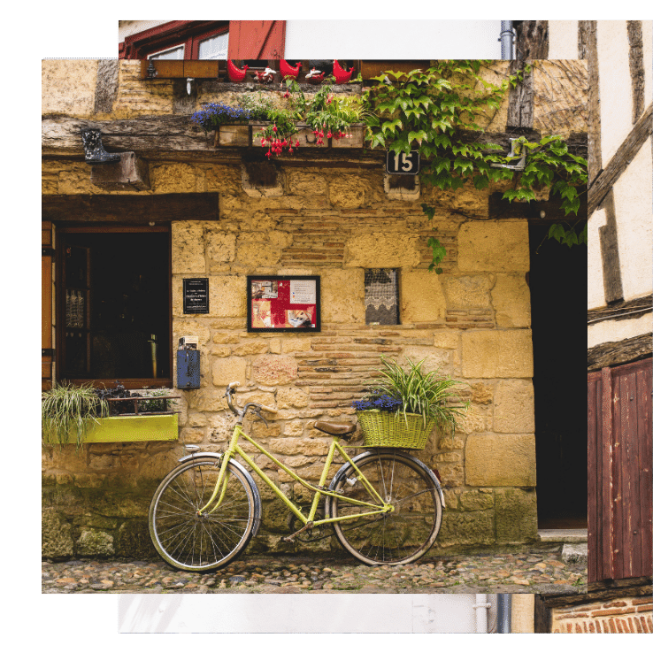 A bicycle lays against a stone building with a pergola on this yoga retreat in France with The Travel Yogi.