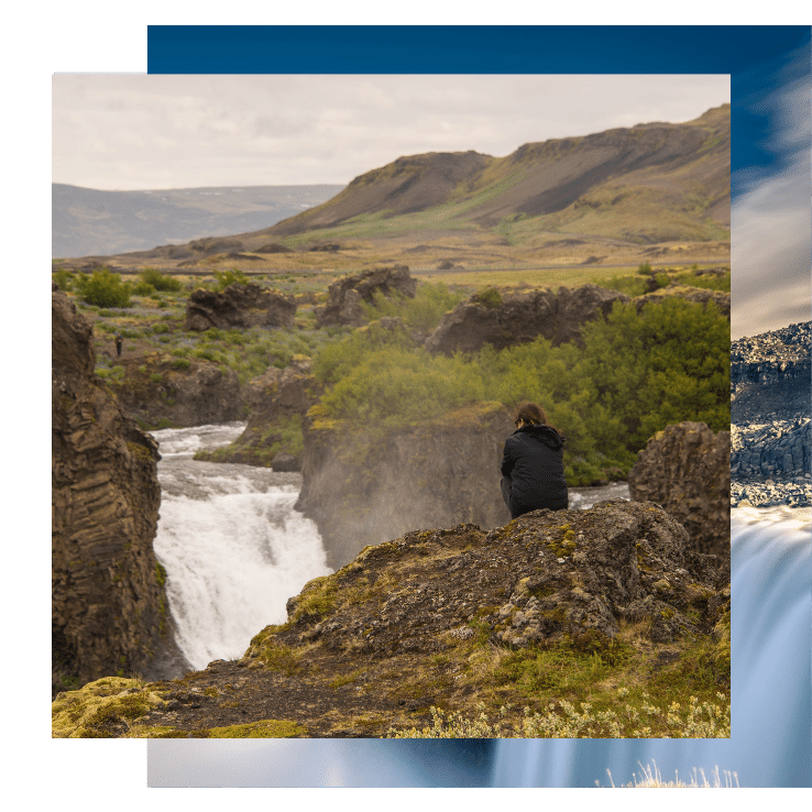 Woman overlooks an icy river on this yoga retreat in Iceland with The Travel Yogi.