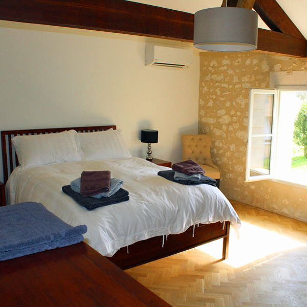 A sunlit bedroom is ready for you on this yoga retreat in France with The Travel Yogi.