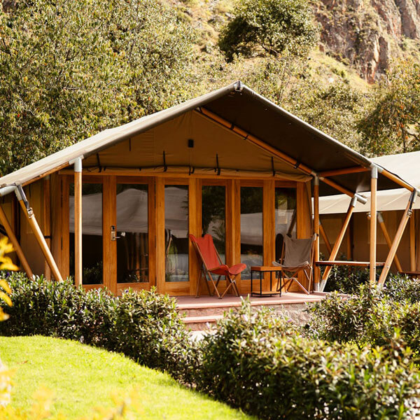 Glamping accommodations at Machu Picchu feature a tent with red chairs on a patio. Explore this Peru yoga retreat with the Travel Yogi