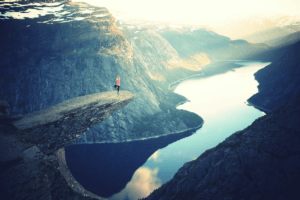 Image of a woman in tree pose on a rock cliff. Learn about wellness travel with The Travel Yogi.