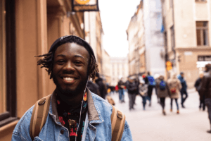 Man walks on a busy street with a backpack and a big smile. Learn why travel is good for your mental health with The Travel Yogi.