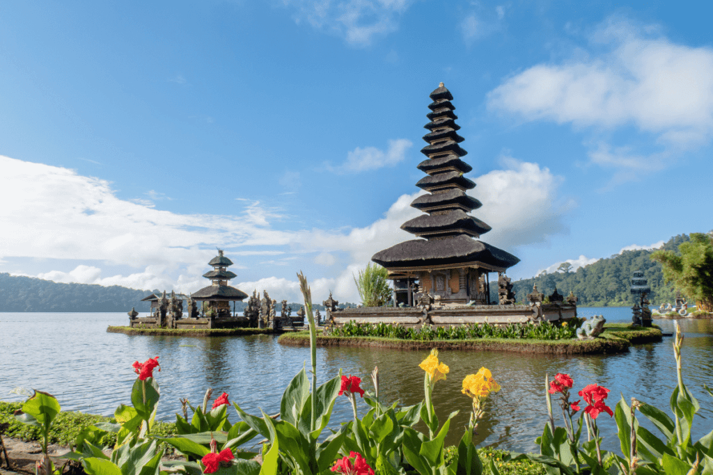 Image of a Balinese temple with colorful flowers in the foreground. Learn Balinese Temple etiquette: The Travel Yogi