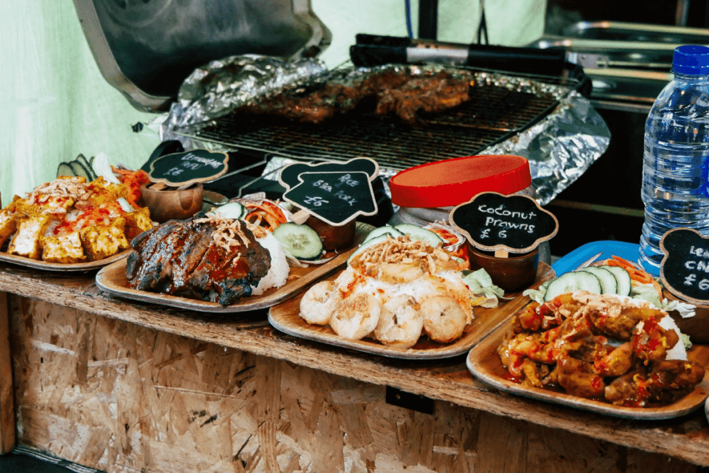 Cooked street foods on wooden plates. Learn how to navigate and prevent tummy bugs while traveling with The Travel Yogi.